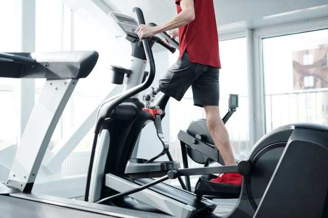person on elliptical machine