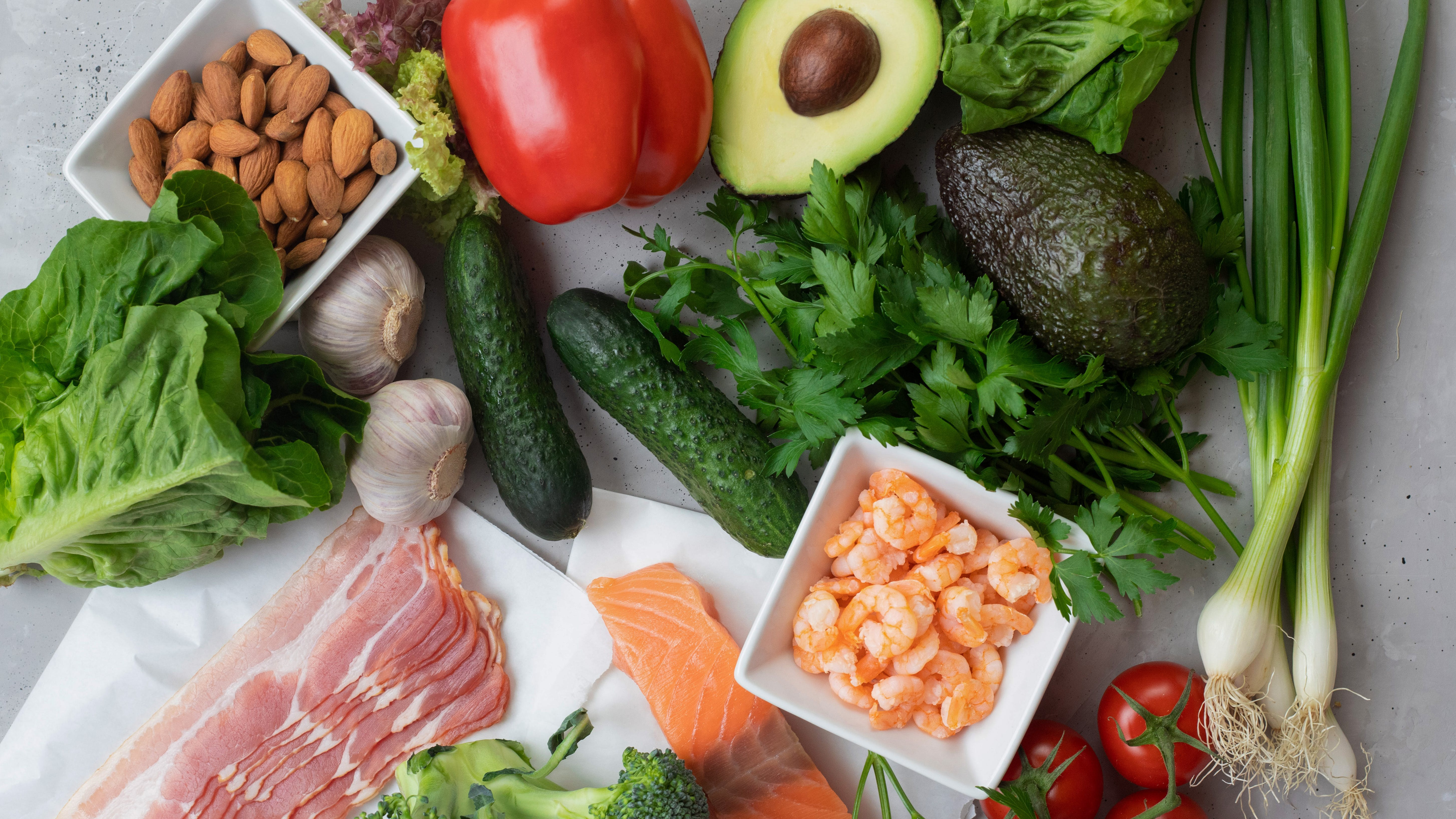 Keto diet concept. A set of keto nutrition products. Fresh vegetables, seafood, bacon and nuts.