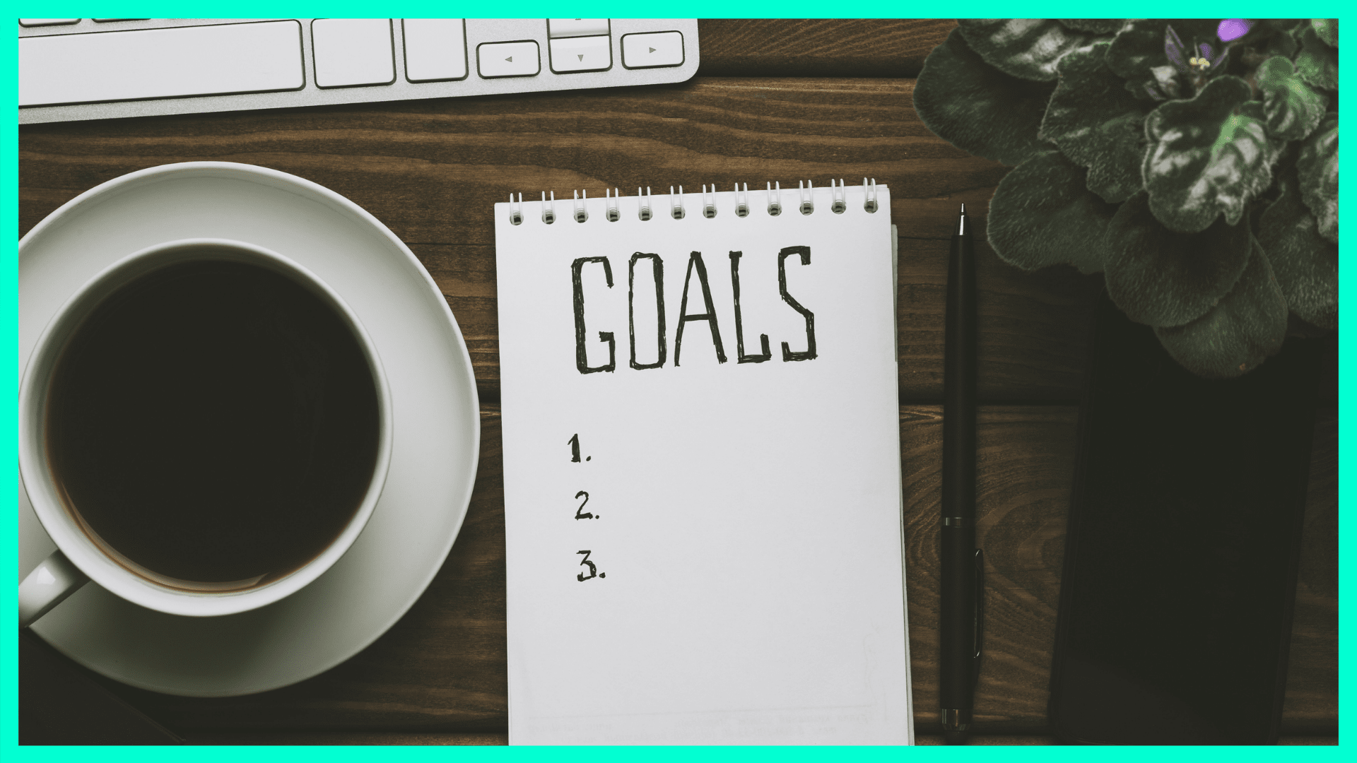 "a notepad that says ""goals"" next to a cup of coffee"